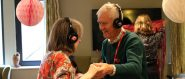 Photograph of two older people wearing headphones and dancing in a room with lots of decorations.
